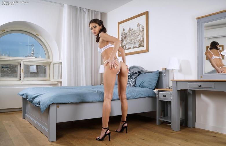 semi professionele luxushure cindy räckelt ihre lange beine auf dem bett picture 2